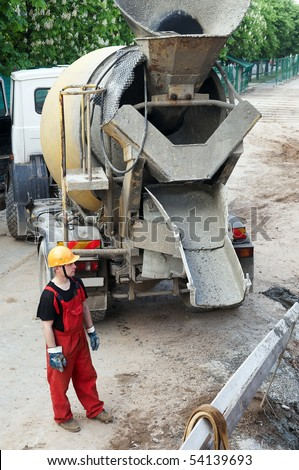 Happy worker builder controlling concrete mixer filling process at construction site - stock photo