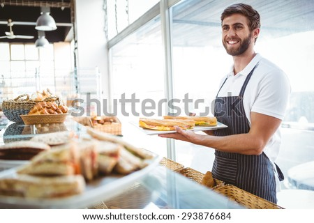 happy worker holding sandwiches at the backery - stock photo