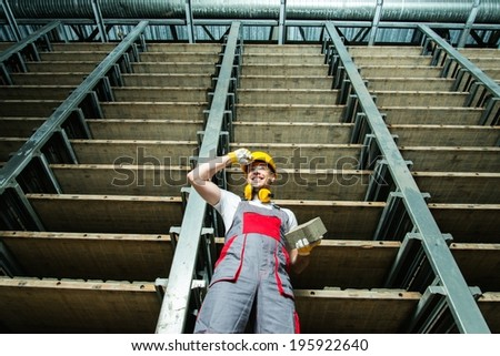 Happy worker in a storage room on a factory  - stock photo