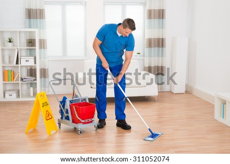 Happy Worker With Cleaning Equipments And Wet Floor Sign In House