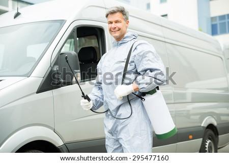 Happy Worker With Pesticide Sprayer Standing In Front Van - stock photo