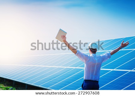 Happy working solar station raising his hands with tablet computer on a background of photovoltaic panels. Science solar energy. - stock photo
