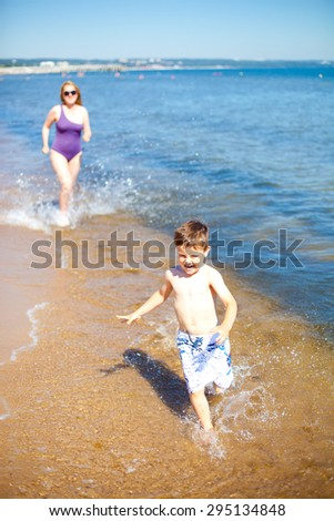 Happy 4 year old boy playing with his mother on the Baltic sea - stock photo