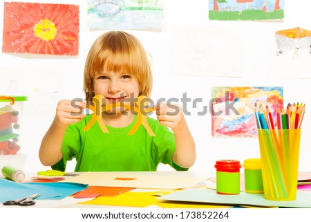 Happy 4 years old boy with paper garland on preschool art lesson - stock photo