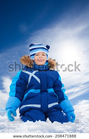 Happy 5 years old Caucasian boy sitting in snow outside in winter - stock photo