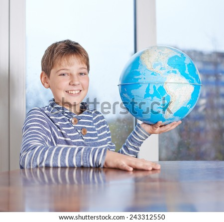 Happy 12 years old children boy sitting at the wooden desk while holding the Earth globe in his hand, composition against the window - stock photo