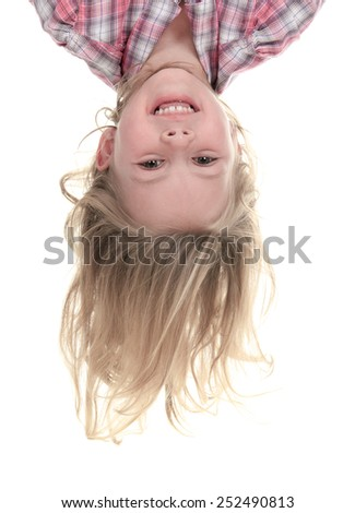 Happy 4 years old girl hanging upside down isolated on white with smile on her face