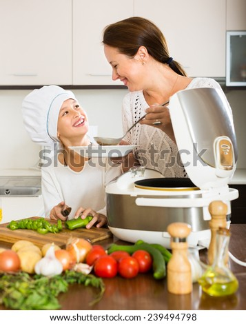 Happy 25-30 years old mother and little daughter using multicooker at kitchen - stock photo