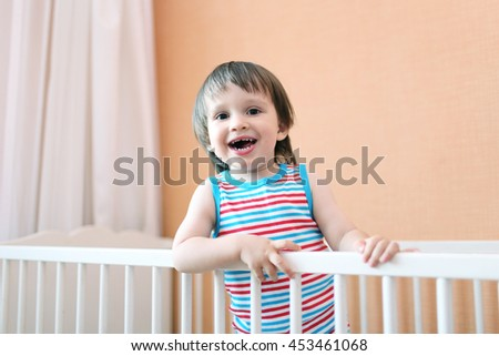 happy 2 years toddler in white bed
