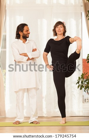 Happy yoga multiethnic couple posing and practicing yoga, in an yoga studio environment full of light.