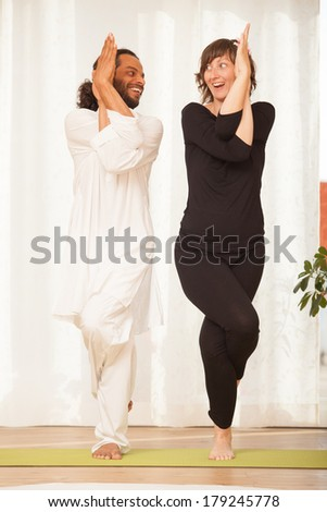 Happy yoga multiethnic couple posing and practicing yoga, in an yoga studio environment full of light. - stock photo