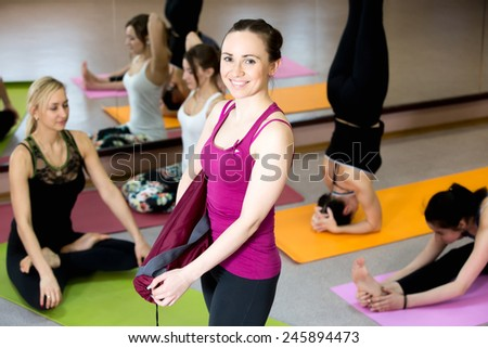 Happy yogi girl holding folded pink yoga mat, her class partners practice various asanas on the background