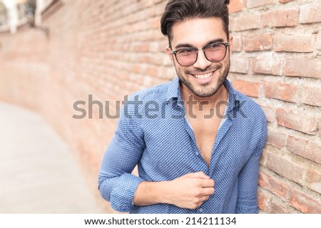 happy youn man with glasses looks to his side and laughs , leaning against brick wall - stock photo