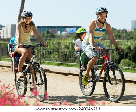 Happy young active family of four cycling on street road in summer day