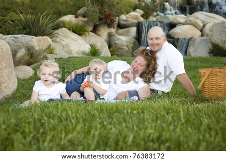 Happy Young Adorable Family with Twins Portrait on Grass in the Park. - stock photo