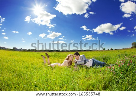 Happy young adult couple in love on the field. Two,  man and woman smiling and resting on the green grass. - stock photo