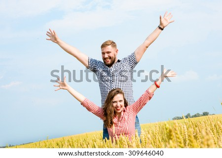 Happy young adult couple in love spending time on the field on sunny day outdoors. Handsome man and beautiful woman enjoying holiday together. Romance and love concept - stock photo