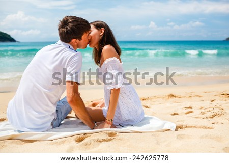 happy young adult couple kissing on a tropical beach - stock photo