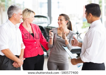 happy young adult daughter receiving a new car from her parents - stock photo