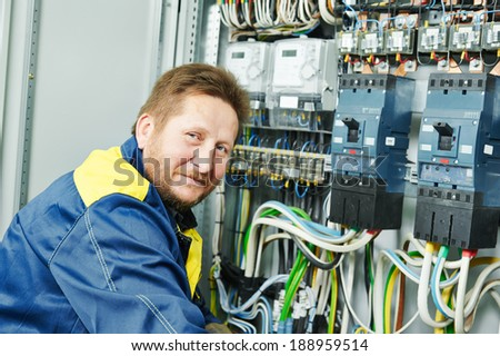Happy young adult electrician builder engineer in front of his co-worker screwing equipment in fuseboard - stock photo