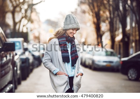 Happy young adult woman walking at beautiful autumn city street wearing colorful scarf and warm hat.