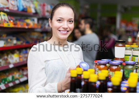 Happy young adults choosing tinned food at supermarket - stock photo
