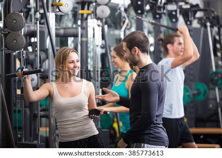 Happy young adults doing powerlifting on machines in modern fitness club