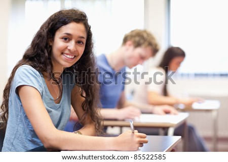 Happy young adults writing in a classroom - stock photo