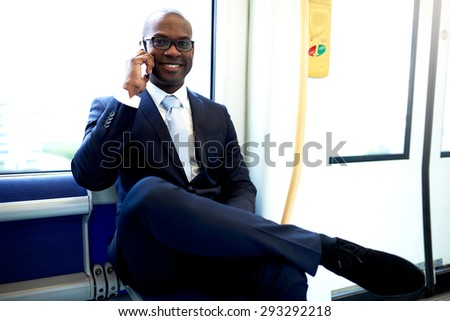 Happy Young African American Businessman Calling Someone on Mobile Phone While Commuting on a Train. - stock photo