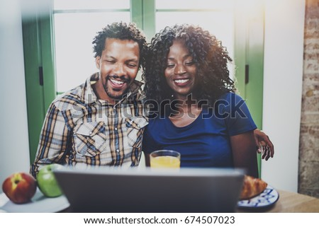 Happy young african american couple having online conversation together via touch tablet at the morning in living room.Smiling black man and his girlfriend using mobile device at home.Flares