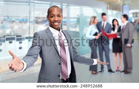 Happy young African-American man in office background - stock photo