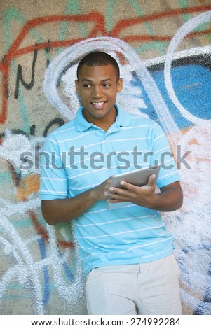 Happy young african american man with digital tablet - stock photo