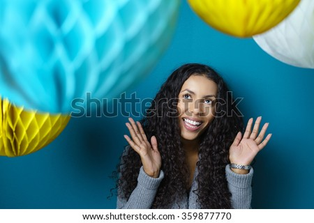 Happy young African American woman at a party celebrating and having fem beneath colorful honeycomb paper hanging decorations over a blue background - stock photo