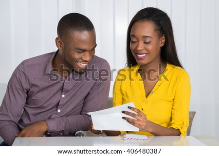 Happy Young African Couple Reading Letter At Home