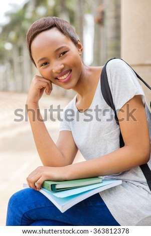 happy young african female college student sitting outdoors