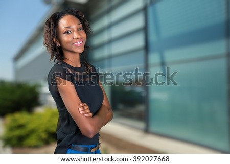 Happy young african woman standing with arms crossed
