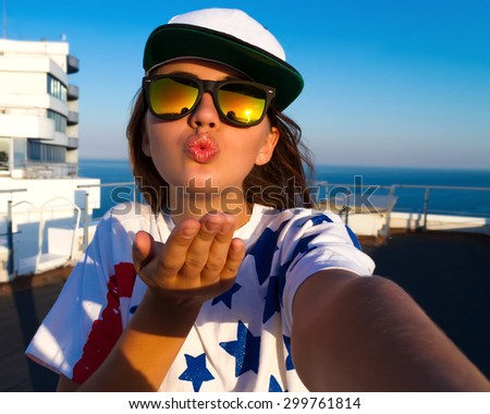Happy young american woman in swag clothes making selfie, sending kisses with her smart phone while posing against amazing sea view background, wearing white cap and american flag printed t-shirt. - stock photo