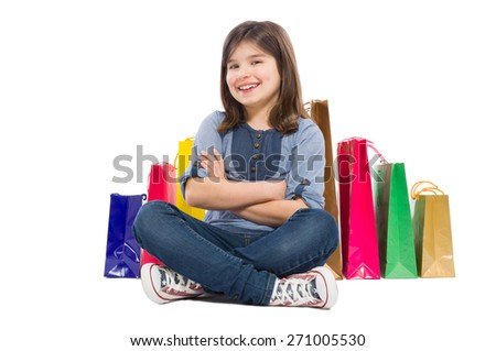 Happy, young and beautiful shopping girl sitting isolated on white studio background - stock photo