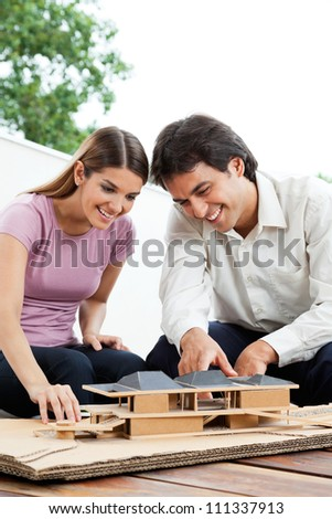 Happy young architects working on a wooden model house together