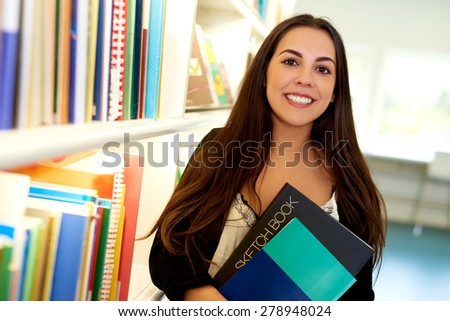 Happy young art student at the college library standing alongside a bookcase full of books with a sketchbook clasped in her arms smiling at the camera