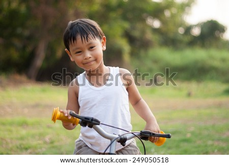 happy young asia boy riding a bike outdoors  - stock photo