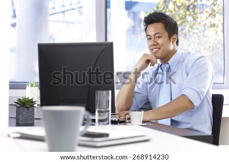 Happy young Asian businessman working with computer, sitting at desk in bright office. - stock photo