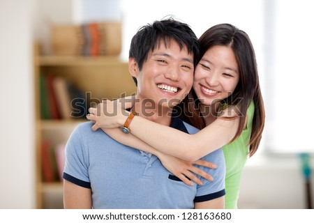 Happy young Asian couple isolated in home background. - stock photo