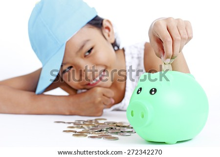 Happy young asian girl saving a coin in a piggy bank. Isolated in white background.
