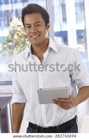 Happy young Asian man holding tablet pc, smiling, looking at camera.