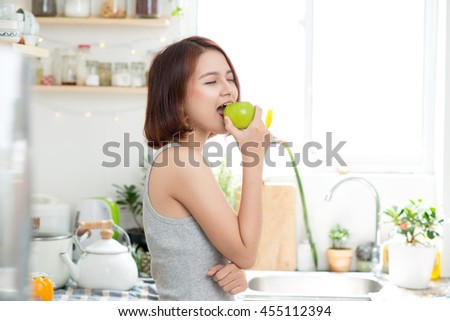 Happy Young Asian Woman Eating Green Apple on Kitchen. Diet. Dieting concept. Healthy food