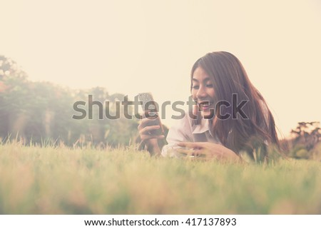 happy young asian woman hold cell phone on grass - vintage style with color paster tone