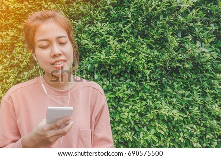 Happy young asian woman listening music with headphones and smart phone on green leaves background