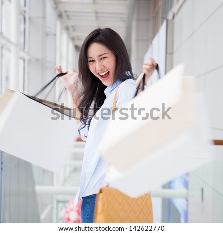 Happy young Asian woman shopping. - stock photo