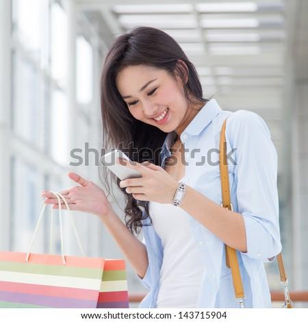 Happy young Asian woman shopping. - stock photo